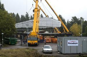 Tre kranar behövs för att lyfta det jättelika väderskyddet som används som tält för takarbetarna.