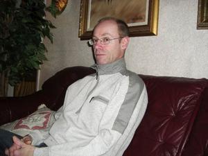 Lars-Åke Lindqvist, var klädd i jeans och en grå jacka med blåa detaljer på. Han är 184 centimeter lång, bär glasögon och är smal.