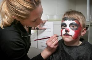 Ansiktsmålning för barnen. Fabian Cavanagh tyckte att det kittlades lite när Emilia Lodén målade honom till en hund.