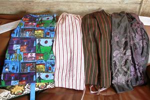 Ett gladmönstrat, afrikanskt förkläde intill mer nordiskt färgade folkdräktsförkläden i bomull, ull och silke.