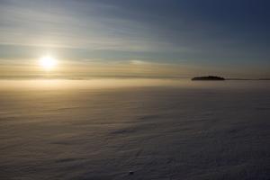 Soluppgång över mälaren med vinterdimman rullandes in mot land.