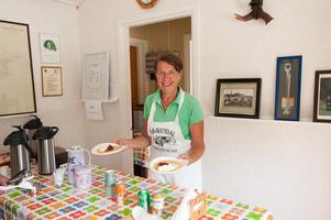 Elfriede Johansson är sommarboende i byn och sköter försäljningen av våfflor. – Det har varit jättemycket folk här, så det gäller att hålla koll på våfflorna, säger hon med ett skratt, men jag är inte ensam säger hon vidare och pekar in mot köket.