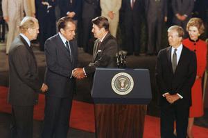 USAs dåvarande president Ronald Reagan, bakom podiet, skakar hand med förra presidenten Richard Nixon medan förra presidenterna Gerald Ford, till vänster, och Jimmy Carter, till höger, ser på. Vita huset i Washington D.C. 8 oktober 1981.  Längst till höger: