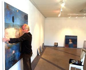 Lars Agger hänger en tavla inför utställningen på Galleri K.