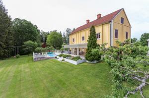 Foto: Malin af Kleen/ Bostadsfotograferna. Bakom det gamla huset ligger en betydligt modernare företeelse - ett poolområde.