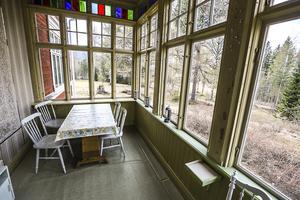 En punschveranda med snickarglädje och en lång rad färgade fönster längst upp.