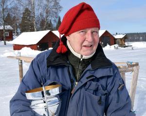Tomas Fredén på Flosjöviken med några av båthusen i bakgrunden.