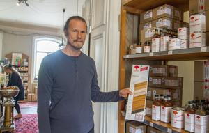 Florian Baumgarten visar upp prover på den ekologiska tyska oljefärgen som säljer bra. Han har själv använt den i flera rum i Herrgården, så som matsalsgolvet.