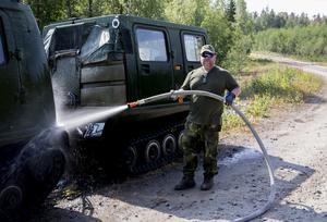 Björn Adelsson från medelpads hemvärn tvättar en bandvagn för att minimera risken  för att smuts ska antändas.