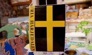 Den flagga som Fria Härjedalen använder med gult kors på svart bakgrund, inspirerad av Härjedalens turistförenings björn.