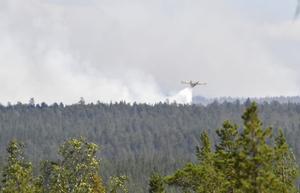Ett flygplan vattenbombar branden.