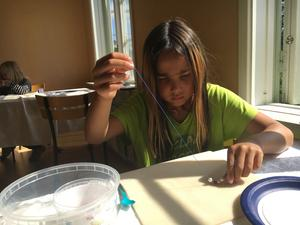 Jasmine Olsson trär tråden med alla de fina pärlor som hon valt för att göra ett halsband.