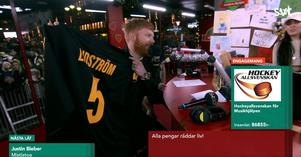 Eriq Christiansson ger över en signerad Lidström-tröja från legendarmatchen mot Viksängsskolan. Foto: Svtplay