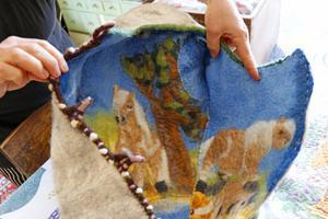 En tovad åkpåse med tovat hästmönster till en baby .
