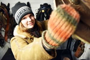 Emelie tar ned en sadel i sin sadelkammare och bod för förvaring och utrustning.