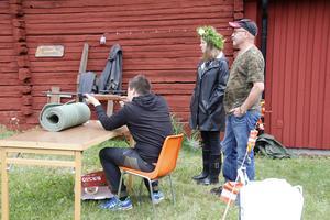 Vid Östervåla hembygdsgård kunde man skjuta luftgevär. Här testar Linus Larsson geväret innan alla midsommarfirare dyker upp.  Bakom honom står Anna Linde och Lars-Ove Pettersson.