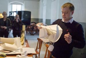 Med några få vana grepp vecklar Niklas Fagerholm ut kartongremsorna till en modern lampa.