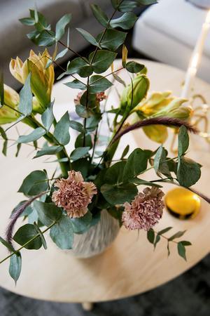 Ett vackert fång med blommor pryder vardagsrumsbordet.