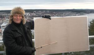Här håller Nicklas Nyberg upp planschen där planerna över Varvsberget visas upp. I nuläget är det väldigt öppet, hälsar Nyberg hemlighetsfullt.