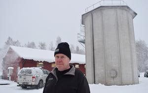 Lars Ryttare framför det gamla reningsverket och den nya silobyggnaden, där mikrodjur – eller bakterier – renar spillvattnet.