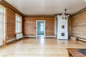 De timrade väggarna är framtagna i vardagsrummet på andra våningen, där det också finns kakelugn.