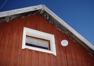 Gunnar tar emot signalen genom en parabolliknande antenn på husväggen.