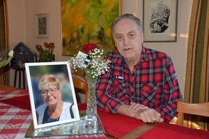Fotografiet på Ingmar Sundmans avlidna hustru Eva, står omgivet av blommor, på bordet i vardagsrummet.
