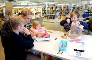 Biblioteksassistenten Adrian Rönnqvist lär Matheus och Maximilian hur det går till att göra en kortfilm medan Ophelia tittar på.
