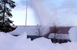 Mängder av snö slungas från taket på Arenaskolan i Timrå.