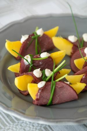Entrérätten, mangobåtar inlindade i rökt strutskött med mangokräm.