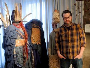 Hemslöjdskonsulenten Fredrik Eriksson visar upp en del av kostymerna som ingår i utställningen Skapartagna och som inspirerade en del av trollspiretillverkarna.
