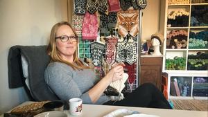 Jenny Alderbrant och hennes man har byggt om ett uthus på gården till lagerlokal för den webbutik med garn och stickmönster som hon driver under namnet Jenny Penny. På spaljén bakom henne syns några av de mönster som hon designat.