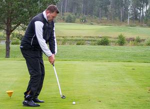 Precis innan slaget. Den vita flaggan på andra sidan vattendraget markerar var koppen är. Här laddar han för en rejäl golfsving.
