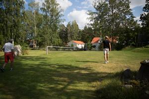 På den stora gräsmattan har de byggt upp en tennisbana.