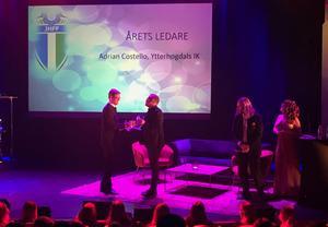 Då Costello inte kunde närvara hämtades utmärkelsen av Magnus Elmqvist från YIKs styrelse.