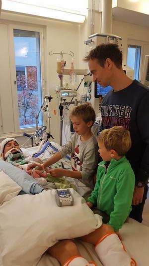 Pappa Rikard och sönerna Hugo och Ivar blickar över svårt skadade mamma Emma och klappar om nyfödda systern Wilma. Foto: Privat.