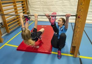 Sveriges bästa gymnastiklärare hjälper en elev med en bakåtvolt under stången.