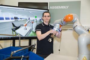 Projektingenjören Juan Luis Jiménez Sánchez från Spanien är också en av flera KTH-studenter som nu fått arbete på Scanias framtidslabb. Här med en robot som kan fungera som en assistent vid en arbetsstation. På skärmen i bakgrunden sker samma sak – men virtuellt.
