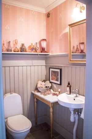 Ett sött badrum med en samling art deco-flaskor på hyllan.