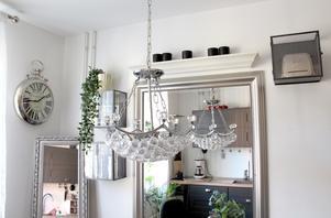 Takkrona med snöbollar, silverramar och tittskåp med fina saker i köket.