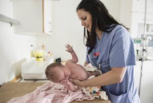 En och en halv dag gammal är det här vackra flickebarnet som barnmorskan Jenny Jansson kontrollerar.