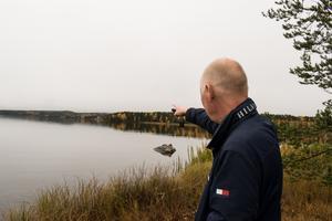 Lars Jerdén pekar mot Källviken och hur en eventuell gångväg skulle kunna följa stranden.