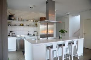 Vitt kök med industrikänsla tack vare den öppna hyllösningen och stolarna bland annat. Foto: Anna-Lena Wickman/Anders Holmberg Arkitekter