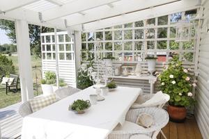Så här ser det ut i dag. Luftigare spaljé, ett ljust tak och glasvägg som skydd mot vinden.  – Här sitter vi väldigt ofta, säger Iréne Wiberg.