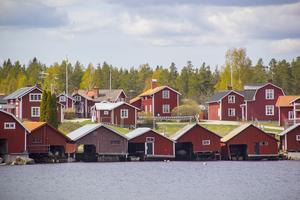 De röda sjöbodarna står på rad längs vattnet i Skärså.