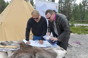 Mattias Jonsson visar ritningarna för Älvdalens tidigare stadsarkitekt Tomas Johnsson.