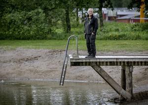 Peter Toth på bryggan till Alnängsbadet. Under honom slingrar sig slangen som fyller på nytt vatten men redan nu är örebroarna välkomna att bada. Det vill säga om de härdar ut i åtta–tiogradigt vatten innan solen värmer på.