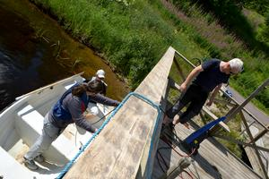 Sommarjobbande ungdomarna Johan Eklund och Ruben Jarefors ger just nu ångbåtsbryggan ett underhållsmässigt lyft. Intresseföreningens Lars Broström arbetsleder.