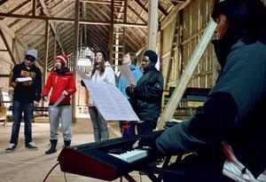 Nästan utomhus. I ladan som hör till Hults lägergård övad ett gäng sångare under ledning av Annica Heerman. Bild: JAN WIJK
