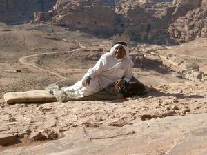 Van att bli fotad av turister är denna beduin som ligger längst ut på klippkanten strax nedanför de högst belägna kungagravarna i klippstaden Petra i Jordanien. Mobilen ligger under filten! Prickarna till höger är människor, säger lite om höjden. Petra anses vara ett av världens sju nya underverk, står med Unescos världsarvslista. Är absolut värt ett besök!